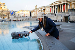 © Licensed to London News Pictures. 02/02/2015. LONDON, UK. People react to frozen water fountains in Trafalgar Square as temperatures drop below zero in London on Monday, 2 February 2015. Photo credit : Tolga Akmen/LNP