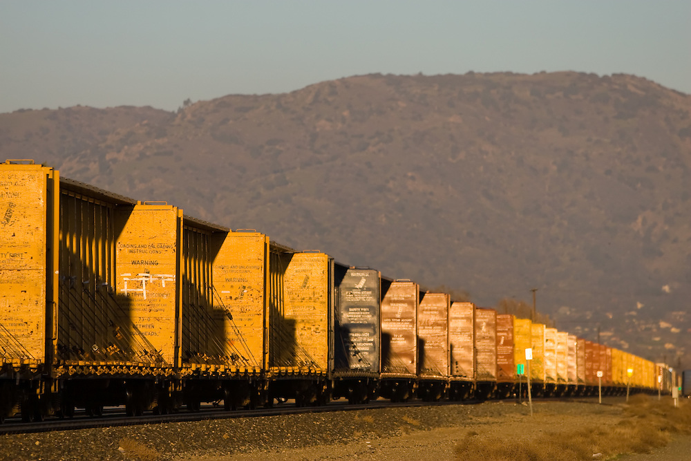 A whole train load of empty lumber cars tops the grade and begins to descend through the Tehachapi Mountains in southern California.