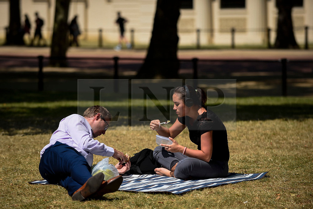 © Licensed to London News Pictures. 16/07/2019. LONDON, UK.  A couple have a picnic in the sunshine in St. James's Park.  Temperatures are forecast to rise to 26C.  Photo credit: Stephen Chung/LNP