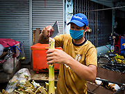 28 MAY 2018 - BANGKOK, THAILAND: A man makes sugar cane juice to sell in Phra Khanong Market in Bangkok. The market serves a mix of Thai working class people and immigrants from Myanmar (Burma).     PHOTO BY JACK KURTZ