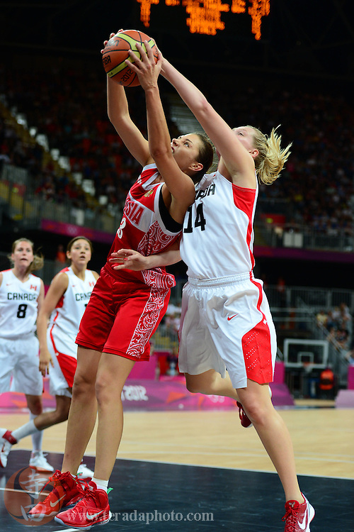 Jul 28, 2012; London, United Kingdom; Russia player Anna Petrakova (left) fights for a rebound with Canada forward Chelsea Aubry (14) during the second half at Basketball Arena. Russia defeated Canada 58-53.