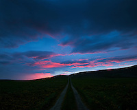 A dirt road by Skálar on Langanes, Northeast Iceland. Pink clouds on sky, taken after sunset.