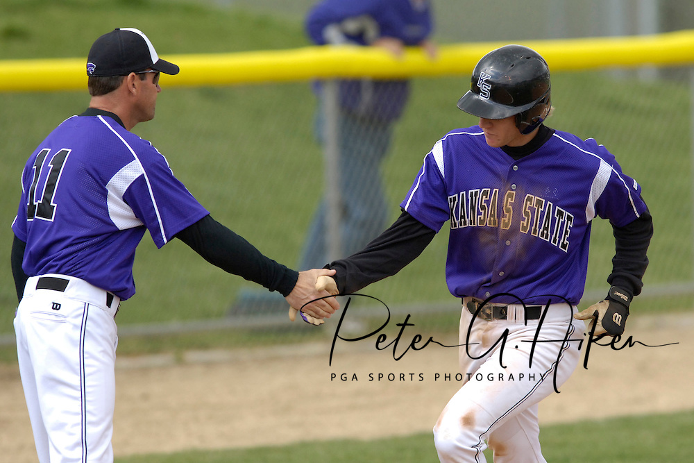 Kansas State head coach Brad Hill (L) shakes Jared Goedert's (R) hand as he rounds third base, after hitting a solo homerun against Oklahoma State in the bottom of the seventh inning.  Oklahoma State defeated K-State 9-4 in 10 innings at Tointon Stadium in Manhattan, Kansas, April 30, 2006.
