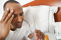 Man with headache in hospital bed