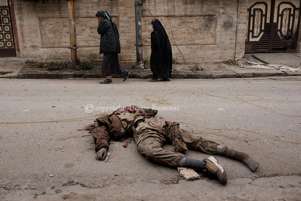 Iraq, Mosul: Mosul residents walk by the dead body of an ISIS fighter in west Mosul. Alessio Romenzi
