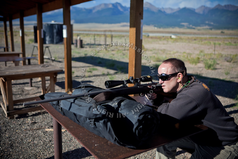 John Daniel Shannon, 48, a former US Army Senior Sniper, is shooting his rifle in a range near his home in Westcliffe, CO, USA, where he retired with his family after a serious brain injury inflicted by an insurgent sniper in Ramadi, Al Anbar Province, Iraq, on November 13th 2004. Daniel fought during the Second Battle of Fallujah and was then moved to nearby Ramadi. Daniel lost his left eye and has multiple health issues because of his injury: memory problems, balance problems, he can't smell and taste well anymore, he suffers from PTSD, has  troubles with large crowds and city surroundings. This is the reason why he and his family moved to a quiet location on the Rocky Mountains. In 2007 Dan helped the Washington Post to uncover patients' neglect at the Walter Reed Army Medical Center; he also testified before Congress. Torrey, 42, his wife, is a freelance writer and a contributor for the Huffington Post; she's also campaigning to improve the situation of veterans' families.