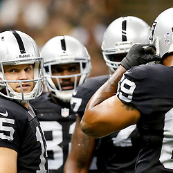 Aug 16, 2013; New Orleans, LA, USA; Oakland Raiders quarterback Matt Flynn (15) in the huddle against the New Orleans Saints during the first quarter of a preseason game at the Mercedes-Benz Superdome. Mandatory Credit: Derick E. Hingle-USA TODAY Sports