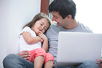 Happy father looking at cute daughter sleeping while using laptop at home