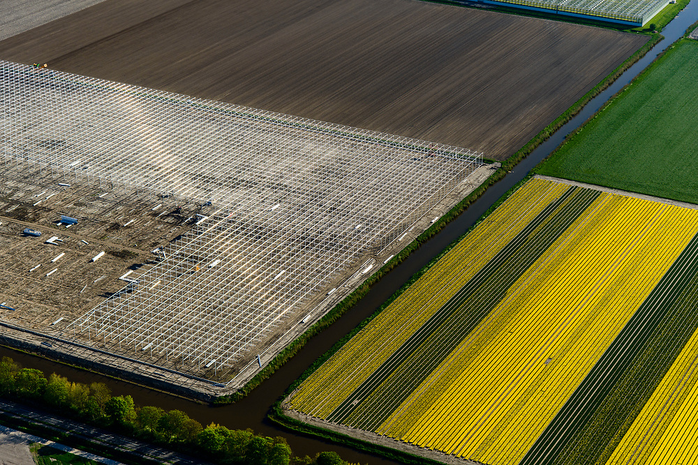Nederland, Noord-Holland, Hollands Kroon, 07-05-2018; bouw nieuwe kassen te midden van bloembollenvelden, nabij Agriport A7.<br /> New greenhouses are being build amidst lower fields, near Agriport A7.<br /> <br /> luchtfoto (toeslag op standaard tarieven);<br /> aerial photo (additional fee required);<br /> copyright foto/photo Siebe Swart