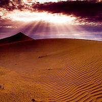 Sunlight shining on sand dunes