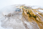 Hot pool in old faithfull hot spring area during winter in Yellowstone