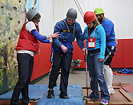 Chris Dougherty (center) of Cedar Rapids is assisted by Jocelen Gudgeon (left), Speech Therapist at University of Iowa Hospitals and Clinics, and Katie Kass (right), Physical Therapist Assistant at St Luke's Hospital, after completing the climbing wall during the Retreat & Refresh Stroke Camp at Camp Courageous in Monticello on Saturday, April 20, 2013. Dougherty had a stroke six years ago.