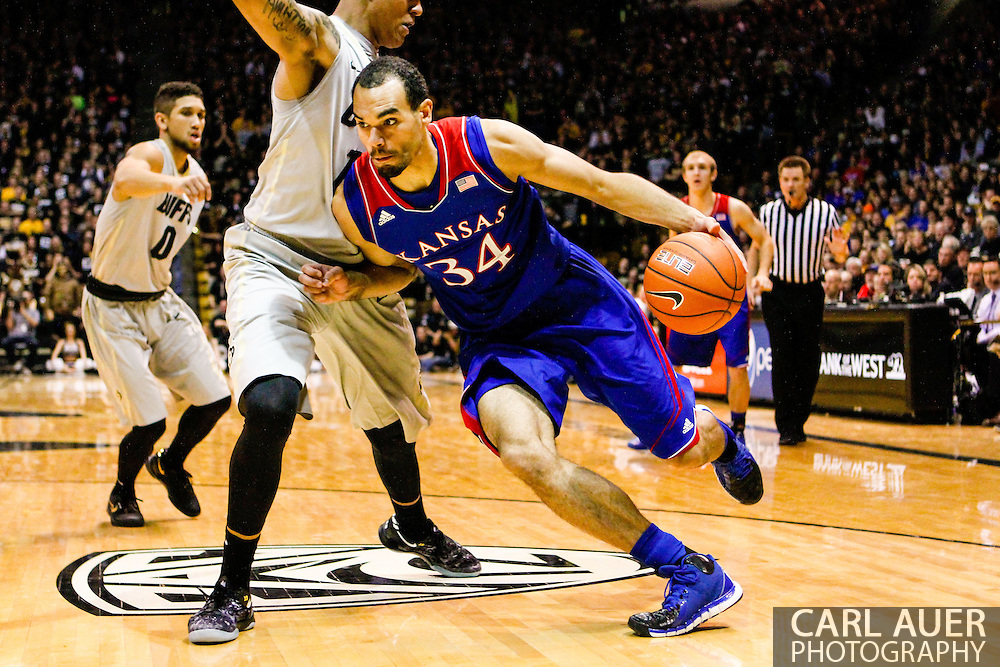 December 7th, 2013:  Kansas Jayhawks sophomore forward Perry Ellis (34) drives the ball against Colorado Buffaloes freshman forward Dustin Thomas (13) in the first half of the NCAA Basketball game between the Kansas Jayhawks and the University of Colorado Buffaloes at the Coors Events Center in Boulder, Colorado