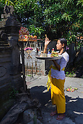 A Balinese woman gives daily offerings and prayers at small altar in Canggu.