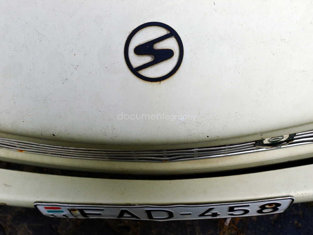 """Close-up details of a Trabant. The name Trabant means """"fellow traveler"""" (Satellite) in Latin; the name was inspired by Soviet Sputnik. The cars are often referred to as the Trabbi or Trabi, pronounced with a short a. It was the most common vehicle in East Germany, and was also exported to countries both inside and outside the communist bloc. The main selling points were that it had room for four adults and luggage, and was compact, light and durable. Despite its poor performance and smoky two-stroke engine, the car has come to be regarded with affection as a symbol of the more positive sides of former East Germany and of the fall of communism, Budapest, Hungary."""