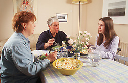 Family group sitting around table eating meal,