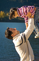 A dad lifts his daughter up to the sky while playing outdoors by Green Lake in Whistler, BC Canada