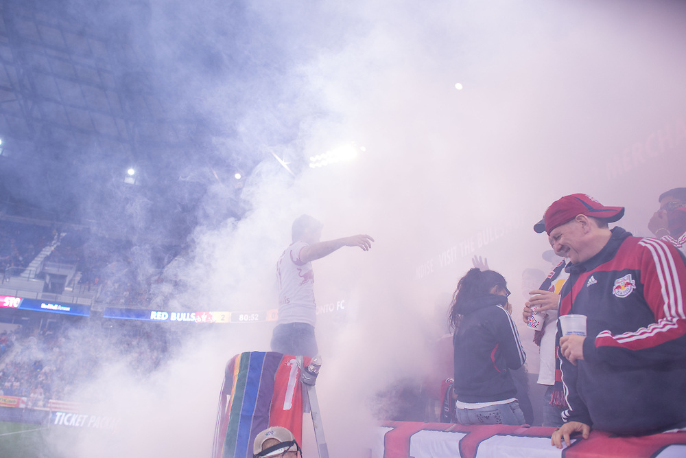 HARRISON, NJ - SEPTEMBER 14:  New York Red Bulls fans cheer on their team after a goal and a smoke bomb going off during the game against the Toronto FC at Red Bulls Arena on September 14, 2013. (Photo By: Rob Tringali)