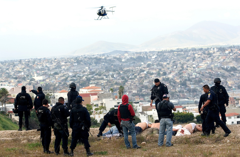 Federal police officers stand over suspects taken into custody in connection with a shooting in Tijuana, Mexico, Monday, March 9, 2009. Mexico's cartels are losing their grip on the prized U.S. drug market, largely because of a cross-border crackdown and a regional shift in worldwide cocaine consumption.