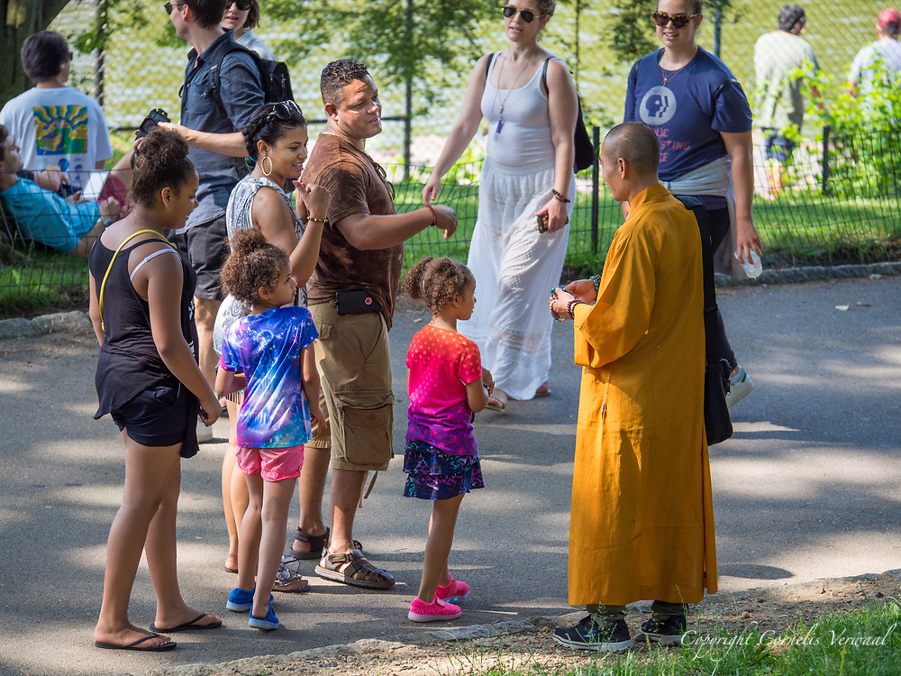 A fake monk interacting with tourists in Central Park.