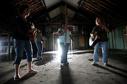 29 August 2007. Lower 9th Ward, New Orleans, Louisiana. <br /> Second anniversary of Hurricane Katrina. The Californian women of 'Indigo Eyes' provide a bit of relief from the sadness. The women play music and sign religious songs in the mostly deserted, empty remains of the  decimated Lower 9th Ward. They stopped and wandered in the gutted Mt Carmel Church. The area remains mostly abandoned and overgrown, ghostly reminders of lives that once were. President Bush came to town and claimed he could be proud of what local and federal government have achieved in the city. Yet two years after the storm, it is quite clear that local and federal government are failing and have a great deal to do to live up their promises.<br /> Photo credit; Charlie Varley.
