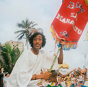Man holding a banner during a street party procession in Brazil