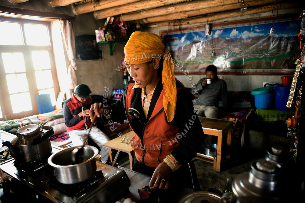A local woman is preparing an omelette for travellers passing by her hut-turned-restaurant along the Leh-Manali Highway...The Leh-Manali Highway is the main road connection between the remote mountainous region of Ladhak, with capital in Leh (3300m), and Manali, HP, a famous hill station 600 km north of New Delhi. Open only four months a year, it is the second-highest motorable road in the world crossing passes up to 5300 meters. It was constructed by the Indian Army in order to develop the surrounding areas as well as monitoring the nearby borders with Kashmir and China. Due to its beauty and increased accessibility, the road to Leh and Ladhak has recently become a must-see destination for local and international tourists leaving the scorching Indian plains..