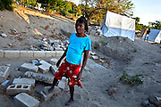 """Esther Dania, 52, single mother of six, lives with her children in a 12-foot tent the International Red Cross gave her right after the flood. The tent is her only possession, along with the clothes she is wearing. """"When my one outfit is dirty, I take it off to wash it and then wear it again,"""" Dania said."""