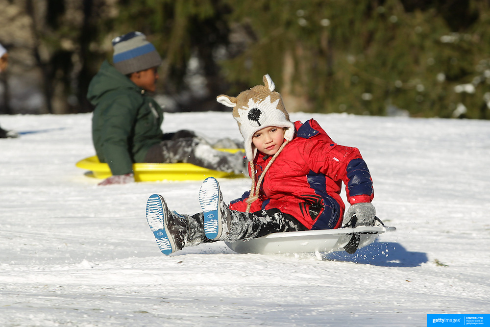 A young child sledding in Central Park after New York City was hit with over 7 inches of snow during its first winter storm of the year. Central Park, Manhattan, New York, USA. 4th January 2014 Photo Tim Clayton