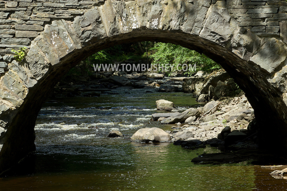 Tusten, New York - The Ten Mile River flows beneath a stone arch bridge on July 24, 2014.  The bridge was constructed in<br /> 1875 when industry at Tusten included<br /> lumbering and the quarrying of bluestone.