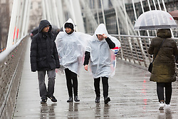 © Licensed to London News Pictures. 03/01/2016. London, UK. People wearing rain ponchos walk across golden millennium bridge in London.  London and the UK has experienced heavy rain and wind today. Photo credit : Vickie Flores/LNP