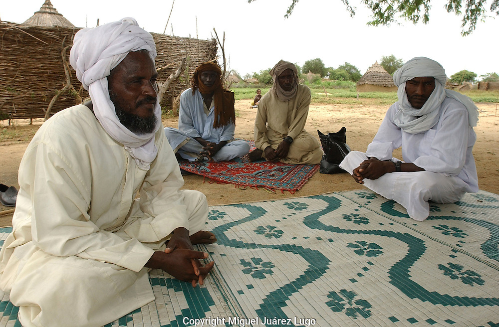 """Abu Gudam, Chad: Sheikh Unis Hussein, left, a leader of a tribe of cow-hearding nomads, said that traditional migration routes to the south are becoming narrower as local farmers plant rice and crops along the route, called a mourhal. He and others believe the government and its allied militias are unfairly targetting Arab nomads--labelling them all 'janjaweed'-- out of fear they might join Chadian rebels. """"They are treating us like we are not Chadians,"""" he said. Chad is home to over 200 different ethnic and linguistic groups. Arabic and French are the official languages. Islam and Christianity are the most widely practiced religions. Chad is one of the poorest and most corrupt countries in the world; most inhabitants live in poverty as subsistence herders and farmers. Since 2003, crude oil has become the country's primary source of export earnings, superseding the traditional cotton industry.    (PHOTO: MIGUEL JUAREZ LUGO)."""