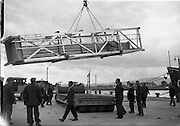 """31/07/1962<br /> 07/31/1962<br /> 31 July 1962<br /> Oil drilling equipment arrives at North Wall, Dublin. Image shows of oil drilling machinery for Ambassador Irish oil being lowered onto a CIE heavy haulage truck from the deck of the """"Kendall""""."""