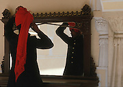 An attendant at the City Palace in Jaipur, India arranges his turban in an ornate mirror.