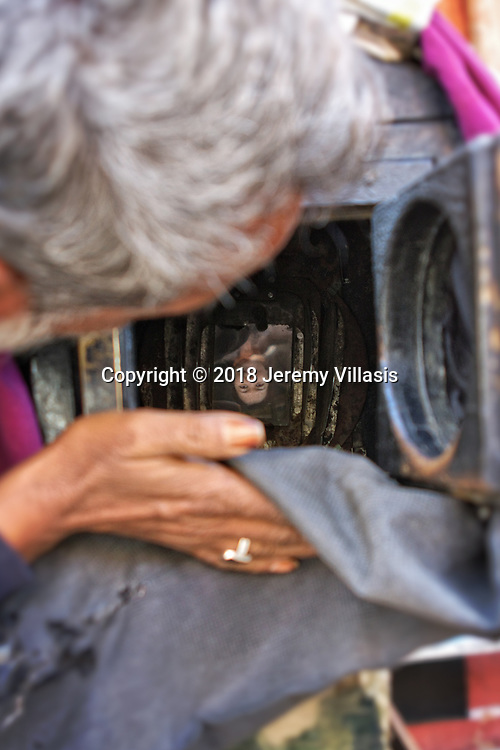 Surendar takes a peek of the upside down image of the customer inside the wooden camera.