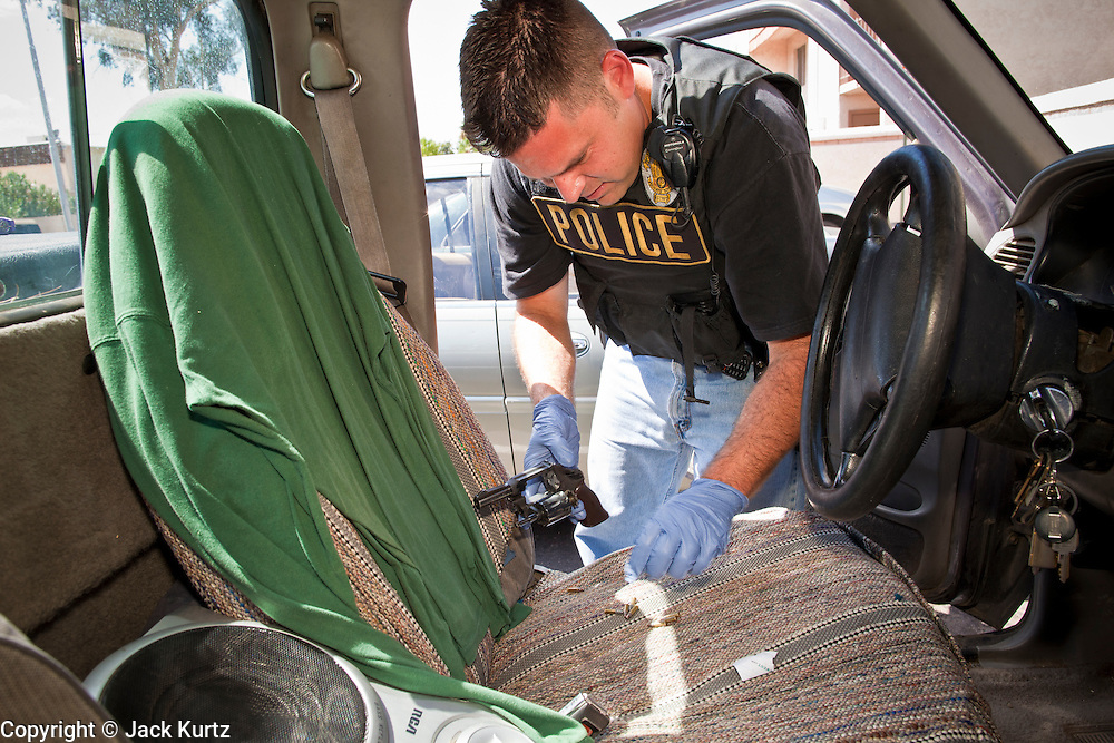 21 SEPTEMBER 2010 - PHOENIX, AZ:  Phoenix detective Dave Dodd (CQ) clears a .22 revolver after finding it on the floor of a truck after they arrested the truck's driver. Crime has steadily dropped in Phoenix over the past few years, in line with national trends. The latest number released this month showed Phoenix reported fewer 2010 homicides, rapes, robberies, thefts - in addition to other major crimes -- compared with the same time period the previous year. Detectives in the Phoenix police department's Major Offender Unit make several arrests every day.  PHOTO BY JACK KURTZ