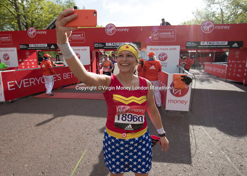 A competitor dressed as Wonder Woman takes a selfie at the finish line. The Virgin Money London Marathon, 23rd April 2017.<br /> <br /> Photo: Jed Leicester for Virgin Money London Marathon<br /> <br /> For further information: media@londonmarathonevents.co.uk