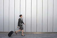 Businesswoman walking outdoors pulling suitcase behind her side view