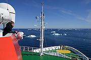 Das Forschungsschiff Maria S. Merian nähert sich dem Probengebiet vor Spitzbergen. Treibeis kann soweit nördlich jederzeit auftauchen. Peter Striewski vom Tauchboot JAGO Team hat die Vorbereitungen abgeschlossen und das Tauchboot ist einsatzbereit. Auch der Blick aufs Meer bereitet für den kommenden Einsatz vor, jede Meeresregion hat seinen eigenen Charakter. Nordatlantik / Arktischen Ozean, Spitzbergen, Norwegen. | The research vessel Maria S. Meria is approaching the sampling area off Spitsbergen. Each marine region is unique and a look at the sea surface is essential for preparing dive operations. This far north, drift ice can occur any time. Peter Striewski, a member of the JAGO team, has completed the preparations and the submersible is ready to dive. North Atlantic / Arctic Ocean, Spitsbergen, Norway.