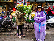 27 DECEMBER 2017 - HANOI, VIETNAM: Selling flowers in the rain in the Old Quarter of Hanoi.      PHOTO BY JACK KURTZ