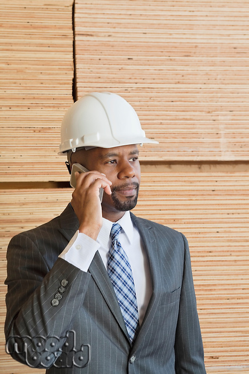 African American male engineer on phone call with stacked wooden planks in background