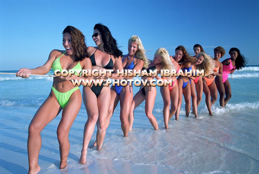 Young women playing tug-of-war in bikinis on beach, Cancun, Mexico