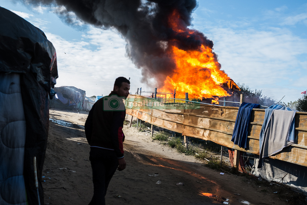 October 25, 2016 - Calais, France - A Migrant passes during the eviction of the Calais Jungle am hut which was set in fire  in Calais, France, on 25 October 2016. Up to the evening, about 4,000 migrants from the Refugee camp on the coast at the English Channel were distributed to several regions in France. The police have begun to tear down the huts and tents in the camp. (Credit Image: © Markus Heine/NurPhoto via ZUMA Press)