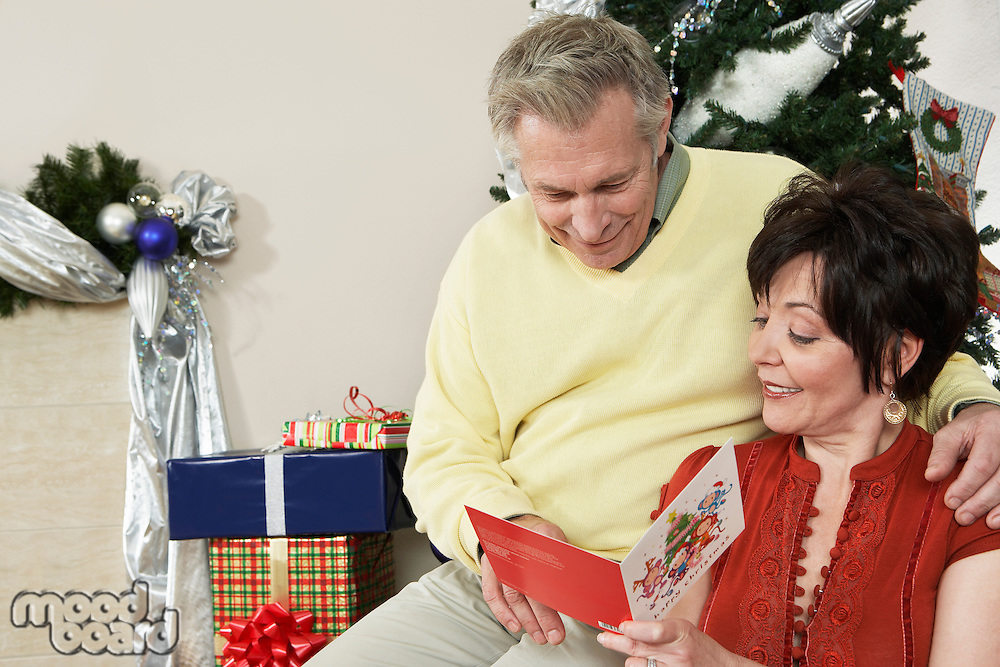 Senior couple looking at Christmas card in front of decorations