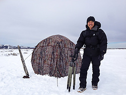 Wildlife photojournalist Noppadol Paothong poses with his blind in south-central Wyoming. ©John L. Dengler / DenglerImages.com