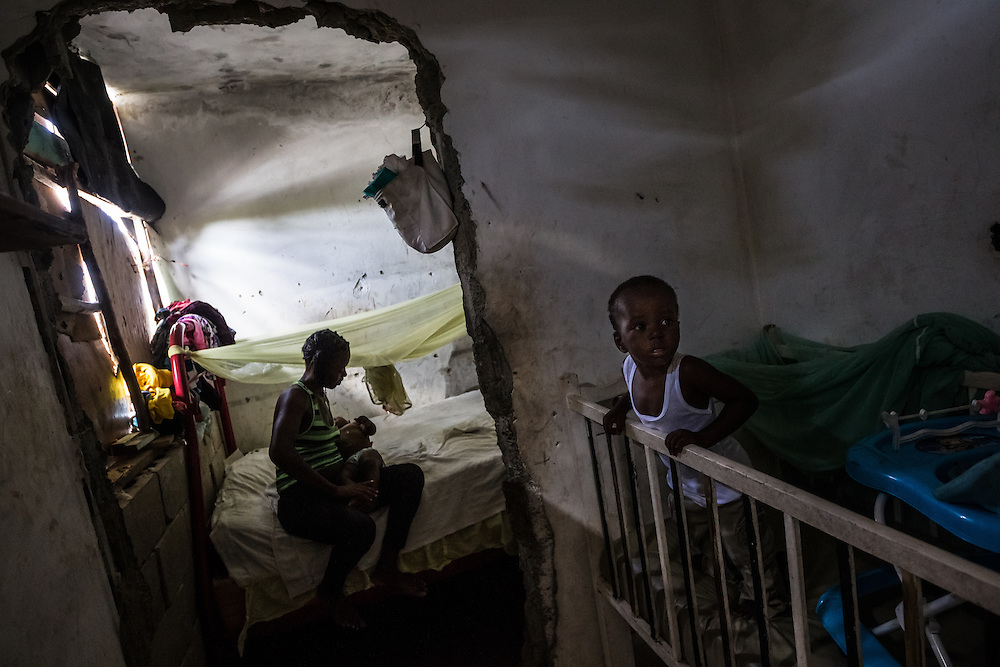 """PUERTO PLATA, DOMINICAN REPUBLIC - JUNE 28, 2015: Fabienne Norasien, 28, lives in the """"penthouse"""", the only apartment on the roof of the resort, with her two small children, Mackensley Desinord, 2, (right) and Fedlina Desinord, 10 months (center). Her apartment is tiny and narrow, with a lumpy bed covered in a yellow mosquito net, a weathered white crib and a small kitchenette with a gas stove. Fabienne was born in Cap-Haïtien, Haiti, and lived with her family selling rice and cooking oil informally in the street, but said they did not make enough money to buy everything that they needed, and often struggled to feed their family. At age 25, she decided to move to the DR and ended up living with other Haitians at the resort.  """"I want to go back to Haiti, I would go back today if it were possible,"""" she said.  """"I came here thinking I would have a better life, but I didn't"""".  """"Many Haitians come here because they think they will find work, but we don't, because we don't have our documents""""."""