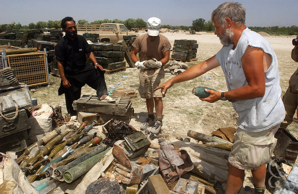 U.S. Special Forces soldiers sort through a variety of captured al-Qaeda weapons that are displayed July 3, 2002 at the Khost airbase in southeastern Afghanistan. U.S. special forces in the region uncovered the weapons as part of a 30 ton cache last week after receiving tips of al-Qaeda activity in the area.