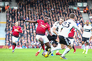 Manchester United Midfielder Paul Pogba battles with Fulham defender Calum Chambers (5) and Fulham defender Joe Bryan (23) during the Premier League match between Fulham and Manchester United at Craven Cottage, London, England on 9 February 2019.