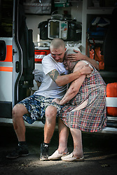 A son tries comfort his mother after she was injured following Ukranian army shelling in downtown of Donetsk, Ukraine, 23 August 2014. Residential areas in several districts of Donetsk, including the central part of the city, suffered from artillery fire, five people was killed and 15 wounded, the press centre of Donetsk city Council reported.