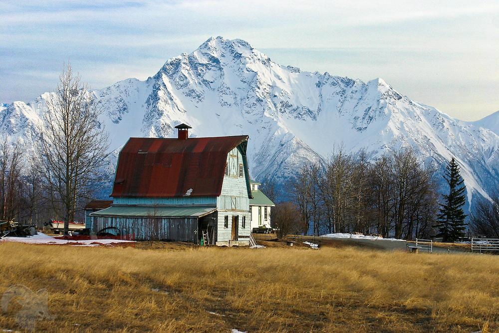 The barn atop Bailey Hill near Palmer, Alaska sits against Pioneer Peak, in the coastal Chugach Mountain Range of Alaska.